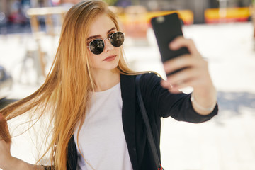 Pretty blonde girl taking selfie on the street