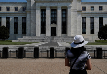 Woman takes a photograph of the Federal Reserve building in Washington