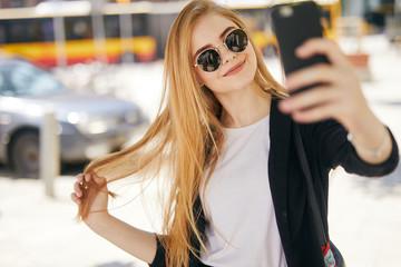 Pretty blonde girl taking selfie on the street