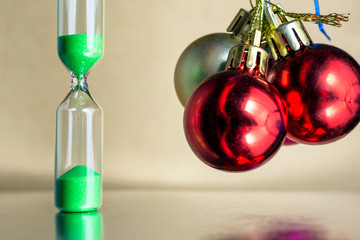 Modern beautiful green hourglass with bright background for copy space. Hourglass time passing concept for christmas or new year deadline, urgency and running out of time.