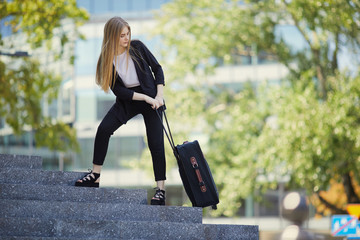 Poster Olive Blonde girl walking on the street with suitcase