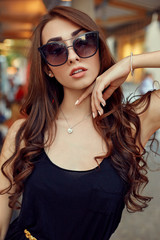 Close-up portrait of young elegant brunette in black dress and sunglasses, touching her face. Fashion street shot