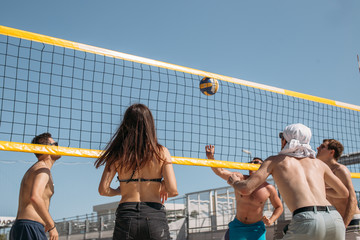 Rear view of unrecognizable caucasian males and females playing amateur beach on blue sky background.