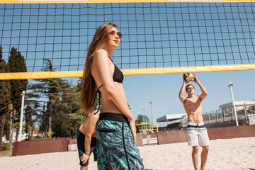 Female beach volleyball player standing near volleyball over net looking at the serving player