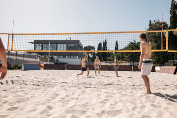 Group of young european people, men and women in swimwear, resting in the same hotel, playing Beach Volleyball, practicing sports activitity lifestyle.