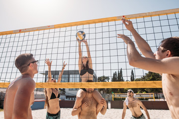 Group of young athletic people playing valleyball at the Resort sandy Court. Active cheerful friends, caucasian men and women enjoying summer holidays on a sandy beach.