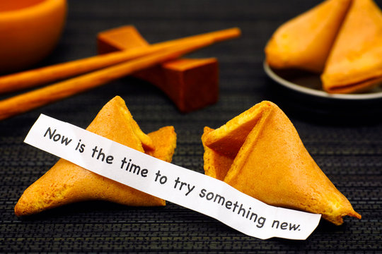 Paper strip with phrase Now is the Time to Try Something New from fortune cookie