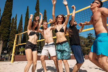 young happy caucasian men and women, being overjoyed with the beach volleyball game win, relaxing and dancing on the sandy court, celebrating success, close up.