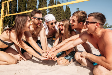 Give high five. Group of fit excited caucasian people talking in a circle, sitting on sand after volleyball game won. discussing goal, achieving team results. Teamwork, vacation, active life benefit