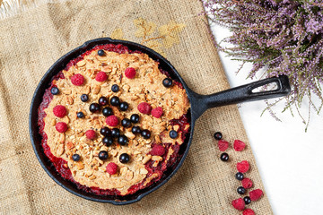 Berry crumble in the black cast-iron frying pan on the white table