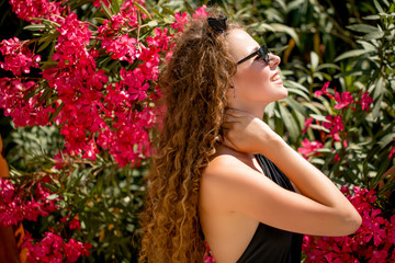 Beautiful female model with perfect hair and slim body against abundantly flowering plants. Concept of summer holiday