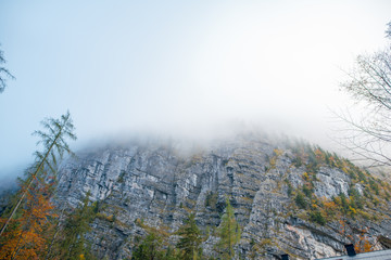 Scenic view from the foot of the mountain. Mountain summit in the fog. Autumn forest. Hallstatt, Austria