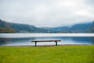 Lonely wooden bench on the lake with wonderful view of autumn mountains with fog and clouds. Hallstatt, Austria