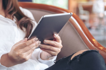 Closeup image of a woman holding and using tablet pc in modern cafe