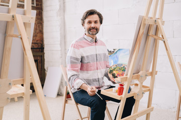 Portrait of mature man painting sitting by easel in art class and smiling looking at camera in studio, copy space