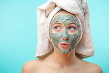 Every decent girl is ready to spent hours treating and caring for her hair and skin before going out night party. Woman with towel on head and facial mask looking at the copyspace over blue background