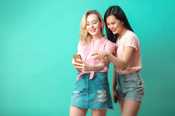 Attractive Thai teenager girl in jeans shorts looking with astonishment while taking selfie with her european girlfriend at studio blue background