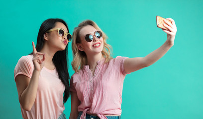 Two diverse teenage girls in summer shorts and sun glasses making selfie, bulging out their lips on blue background with copyspace.