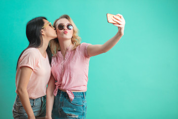 Thai young woman kissing his caucasian blonde girlfriend in sunglasses with duck lips while shooting selfie isolated on blue background.