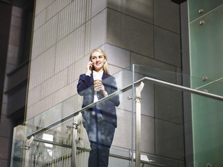 young caucasian business woman talking on cellphone on top of stairs