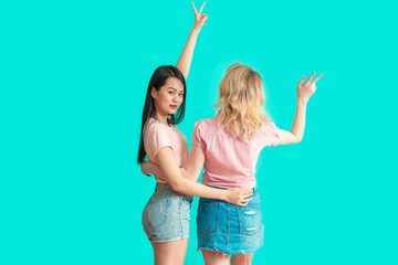 back studio shot of two young mix-race girlfriends, pointing with raised arms to blank space on blue background. Asian woman turns back, looking at camera