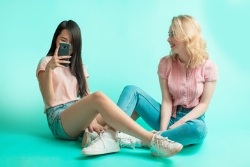 Portrait of a two interracial joyful females with black and blonde long hait and slim bodies, taking selfie while sitting on blue floor