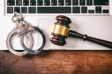 Handcuffs and a gavel on a computer on a wooden background, copy space.