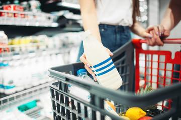 Couple put milk into the cart, supermarket
