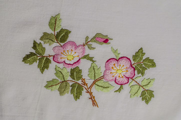 Sprig with pink flowers tea roses with a bud and leaves, embroidered a satin stitch on rough cotton fabric