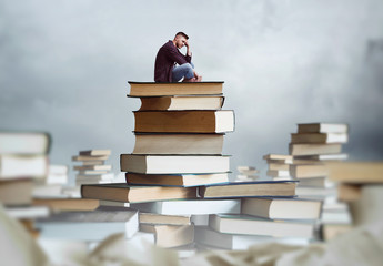Man sits on a stack of books