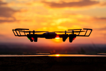 unmanned drone on the background of a sunset in flight