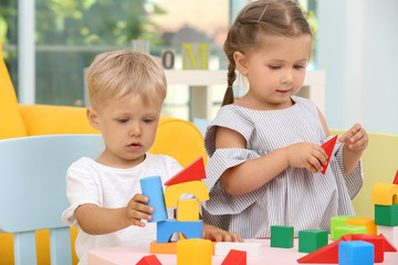 Cute children playing with constructor on table at home
