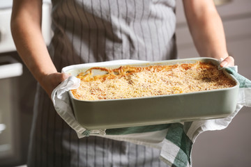 Woman holding baking tray with spinach lasagna in kitchen