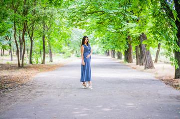 The brunette girl in a blue long dress is standing in the park on a dirt track in full growth