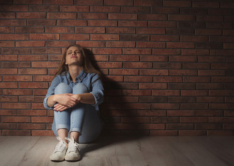 Depressed young woman sitting on floor near brick wall
