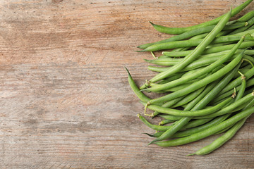 Fresh green French beans on wooden table
