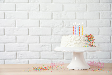 Birthday cake with candles on table against brick wall