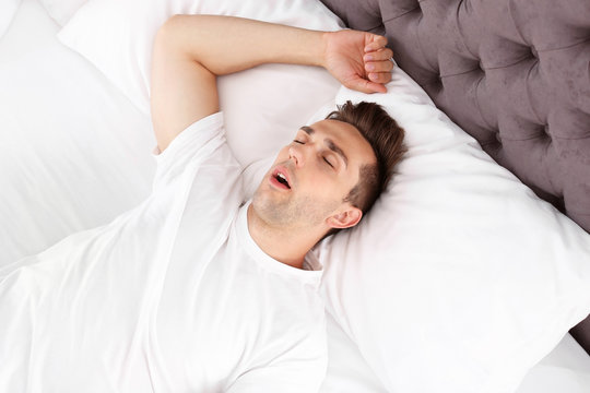 Young man sleeping in bed at home, top view