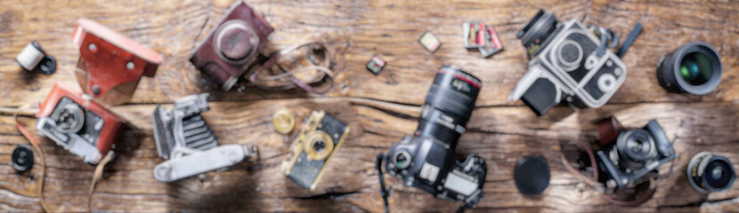 Blurred panoramic picture of different photo cameras on wood.