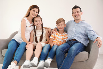 Happy family with cute children on sofa at home