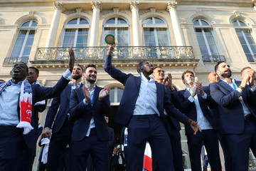 France's midfielder Paul Pogba holds the winner's trophy as he stands with his teammates during an official reception at the Elysee Presidential Palace in Paris