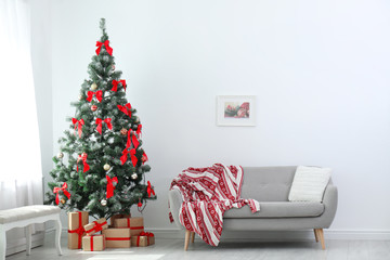 Stylish living room interior with decorated Christmas tree and comfortable sofa