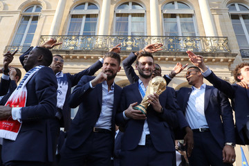 France's goalkeeper Hugo Lloris holds the winner's trophy as he stands next to France's forward Olivier Giroud during an official reception at the Elysee Presidential Palace in Paris
