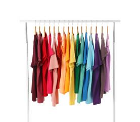 Many t-shirts hanging in order of rainbow colors on white background