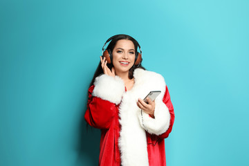 Young woman in Santa costume listening to Christmas music on color background