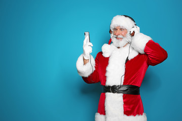 Santa Claus listening to Christmas music on color background