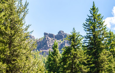 Jagged mountain peak in Hyalite Canyon near Bozeman, Montana framed by green trees