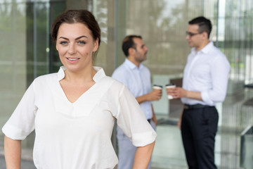 Portrait of happy mid adult female leader standing at office building and smiling, businessmen talking in background. Pretty Caucasian businesswoman wearing white shirt. Female leader concept