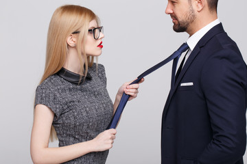 Sexy manipulator woman pulling man by tie