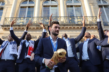 France's goalkeeper Hugo Lloris holds the winner's trophy in front of his team mates in the grounds of the Elysee Presidential Palace during an official reception in Paris